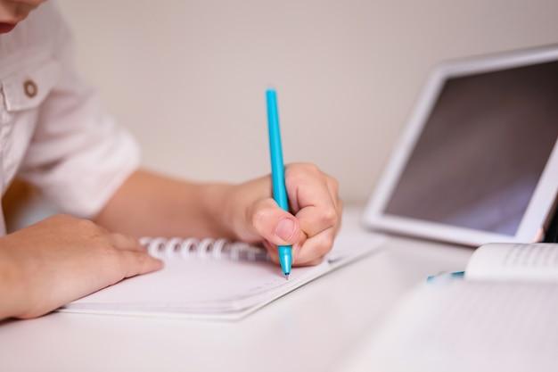 手書きパッドでメモをとる子供の手のクローズアップ