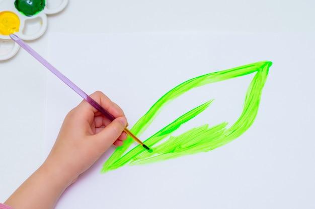 Крупным планом ребенок рисует зеленый лист акварелью на белой бумаге. концепция дня земли. вид сверху.