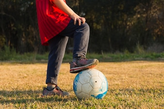 Close-up of child playing with football in park