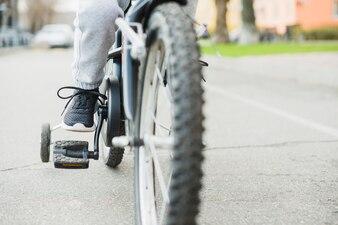 Close up of child riding bike outside
