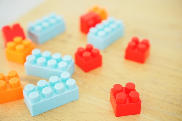 Закройте вверх рук ребенка играя с красочными игрушками соединителя на таблице. развивающие игрушки для детей дошкольного и детского сада.