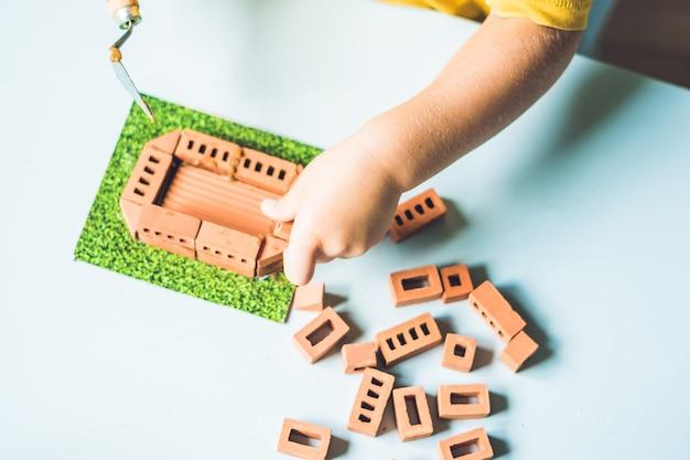 テーブルで本物の小さな粘土レンガで遊んでいる子供の手のクローズアップ