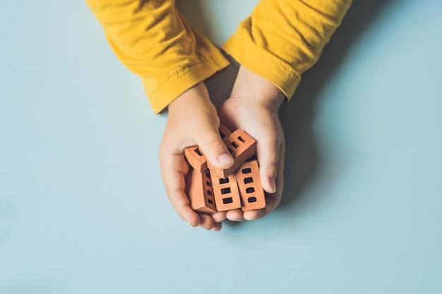 테이블에 진짜 작은 점토 벽돌을 가지고 노는 아이의 손을 가까이