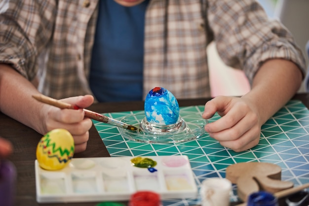 Крупный план ребенка, сидящего за столом и украшающего яйцо красками на праздник пасхи