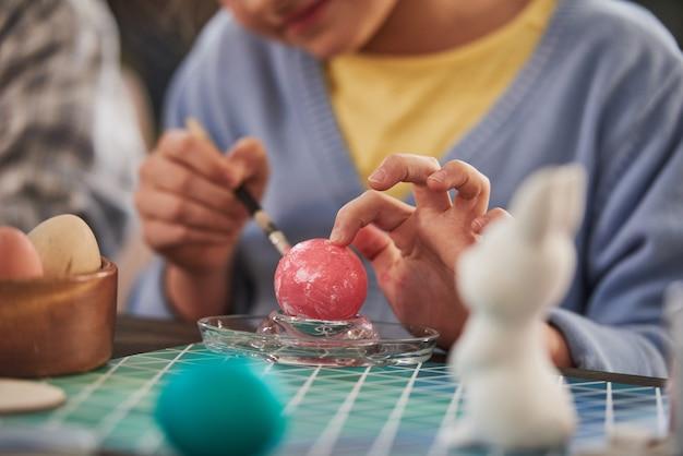 Крупный план ребенка, сидящего за столом, работающего с красками и кистью и украшающего яйцо на пасху