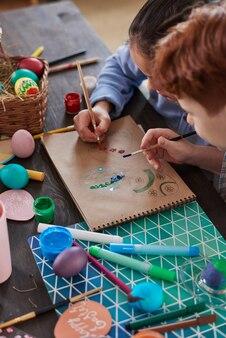 Крупный план детей, рисующих пасхальные яйца на бумаге, сидя за столом