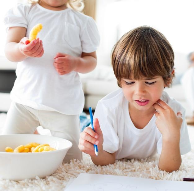 Крупный план детей, которые едят чипсы и рисуют
