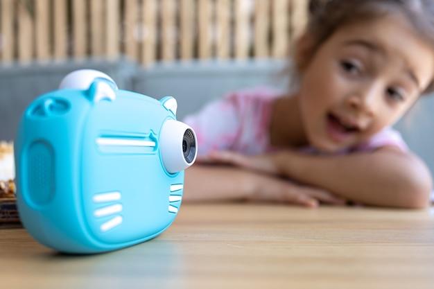 Крупный план голубой игрушечной детской камеры для моментальной печати фотографий.