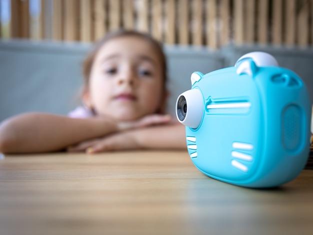 즉석 사진 인쇄를 위한 어린이용 파란색 장난감 카메라의 클로즈업.