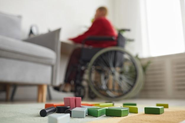 Крупным планом детские игрушки на полу с женщиной-инвалидом, работающей из дома в фоновом режиме, копией пространства