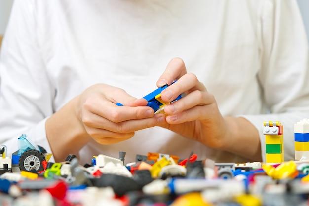 Крупным планом детские руки, играющие с красочными пластиковыми кубиками за столом, развитие мелкой моторики у детей, благоприятных для развития мозговой активности, развивающие игрушки
