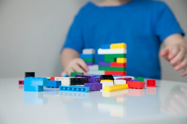 テーブルでカラフルなプラスチック製のレンガで遊んでいる子供の手のクローズアップ。
