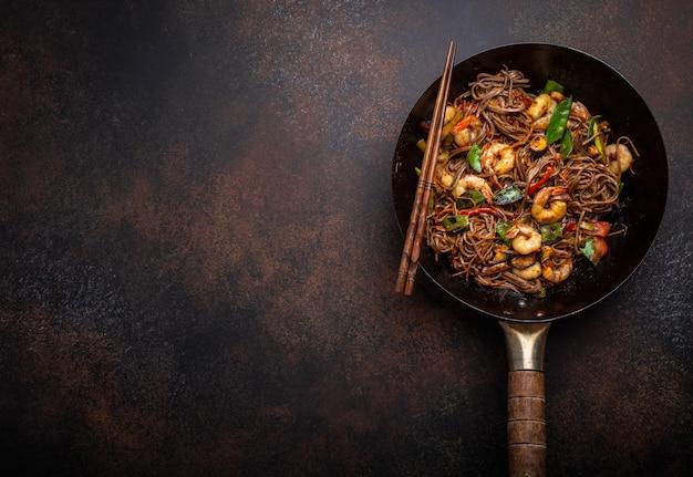 エビと野菜の古い素朴な中華鍋鍋で提供される中国のそば炒め麺のクローズアップ、クローズアップ、上面図。伝統的なアジア/タイ料理、テキストのためのスペース