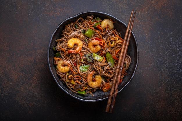 中国のそば炒め麺とエビのクローズアップ、素朴なセラミックボウルパンの野菜をコンクリートの背景に添えて、クローズアップ、上面図。伝統的なアジア/タイ料理、中華料理