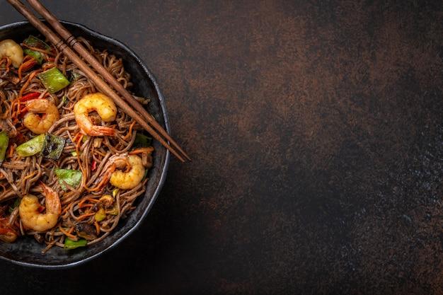 中国のそば炒め麺とエビのクローズアップ、素朴なセラミックボウルパンの野菜をコンクリートの背景に添えて、クローズアップ、上面図。伝統的なアジア/タイ料理、テキストのためのスペース