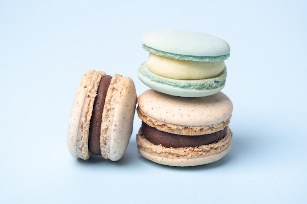 파란색 배경에 초콜릿과 블루 치즈 마카롱을 닫습니다. 맛있는 프랑스 마카롱 - 이미지