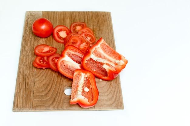 まな板の上に刻んだ新鮮な完熟トマトとコショウの切り刻みのクローズアップ