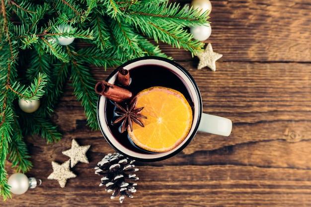 クリスマスと新年のクローズアップは、緑のクリスマスツリーの横にある木製のテーブルでホットワイン、ホットワイン、パンチ、またはお茶を飲みます。スペースをコピーします。