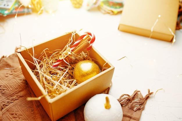 크리스마스 구성 갈색 따뜻한 담요와 새해 황금 볼 롤리팝이 있는 선물 상자를 닫습니다...