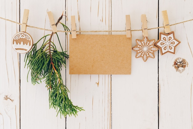 クリスマスの装飾とウッドの背景に掛かっている空白の紙カードのクローズアップ。