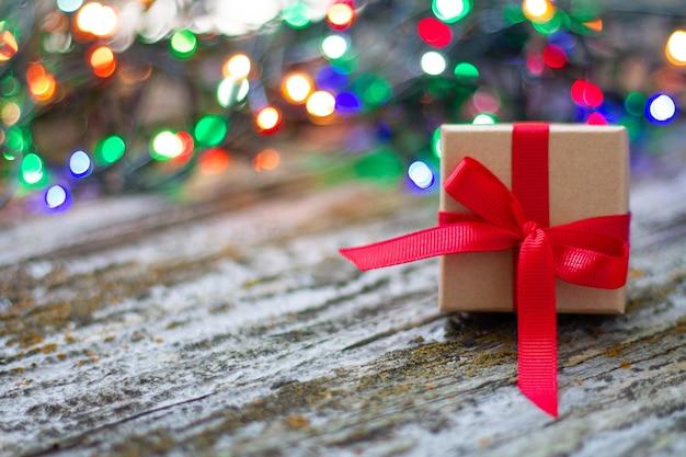 Крупный план рождественской подарочной коробке с красной лентой на деревянном деревенском столе с красочным фоном боке