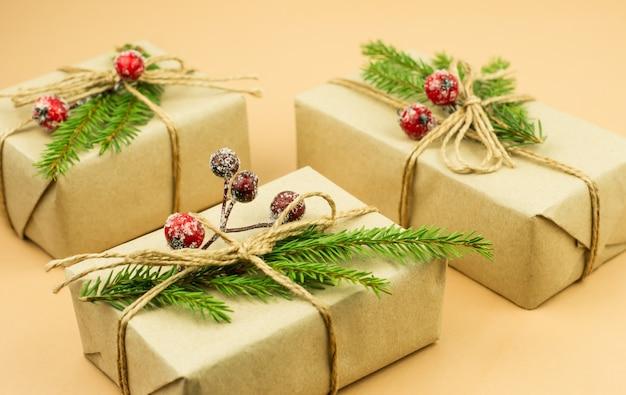 전나무 나뭇가지와 크랜베리로 장식된 공예 종이에 싸인 크리스마스 선물을 닫습니다. 축제 인사말 카드 및 휴일 개념