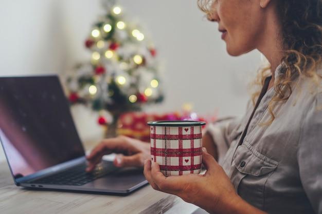 お茶やコーヒーと一緒にクリスマスマグカップと自宅のコンピューターのラップトップで一人で働いている幸せな女性のクローズアップ。インターネットを使用して休日12月シーズンの若い大人の女性