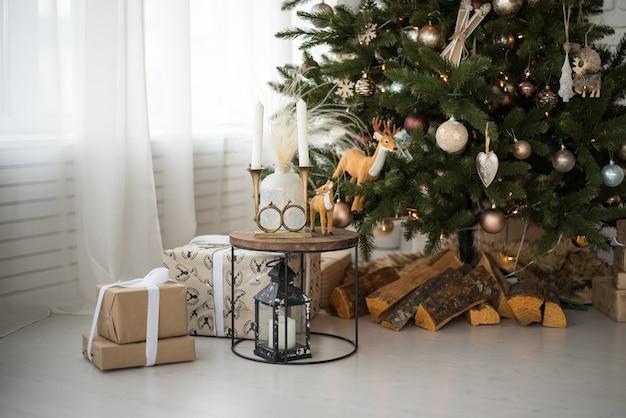 クリスマスツリーの下の床には、包装紙でクリスマスプレゼントのクローズアップがあります。
