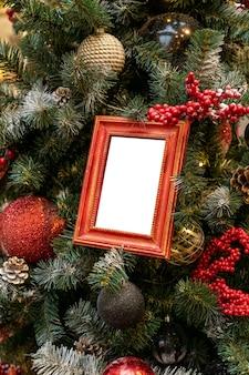 빨간색, 은색, 빈 사진 프레임 모형으로 장식된 크리스마스 트리를 닫습니다. 겨울 인사말 카드의 축제 개념