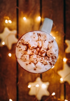 ホットココア、紅茶またはコーヒーとマシュマロとクリスマスの白いマグカップのクローズアップ。冬とクリスマスの時間の概念。