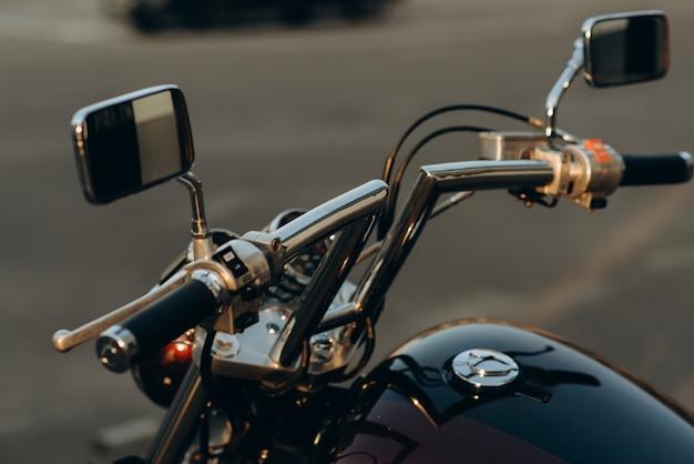 오토바이의 크롬 핸들바 클로즈업. 크롬 디테일이 있는 세련된 맞춤형 초퍼 모토바이크. 부드러운 선택적 초점입니다.