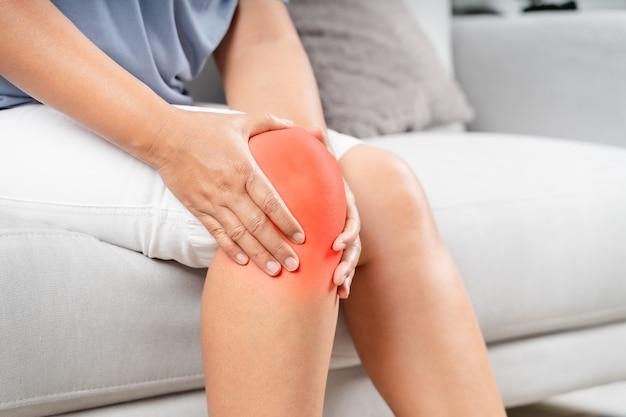 통통한 여성이 소파에 앉아 무릎 통증을 느끼고 무릎을 마사지합니다. 의료 및 의료 개념입니다.