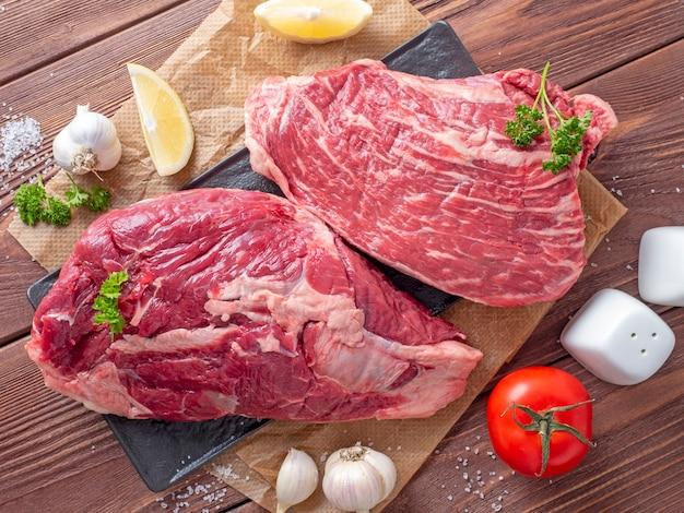 羊皮紙のジューシーな生の牛肉の塊のクローズアップ。周りの野菜やスパイス。食品組成。上面図、フラットレイ。