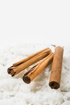 Close-up of cinnamon sticks on steamed white rice