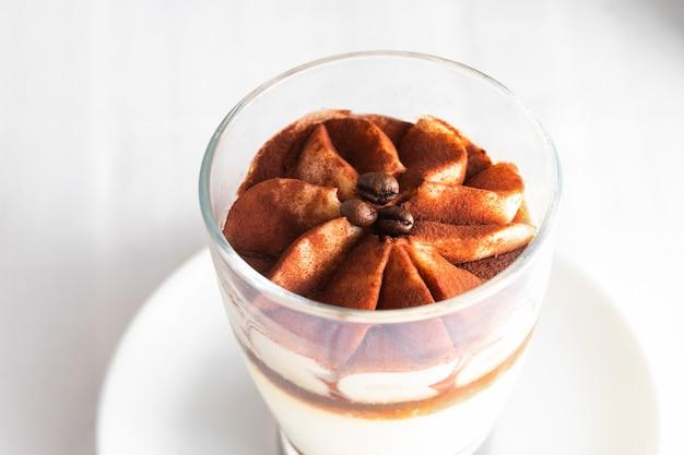 Закройте вверх классического торта тирамису в стекле на конкретной предпосылке.