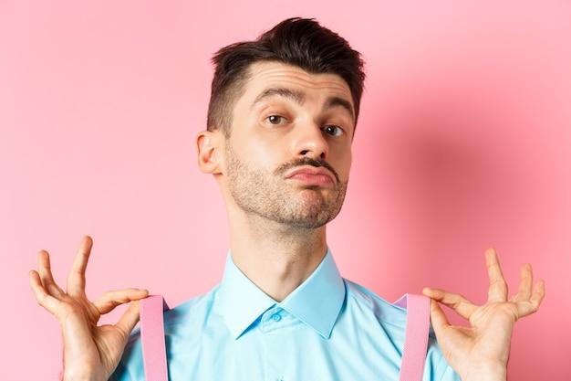 上品なハンサムな男のサスペンダー、パッカーの唇を調整し、あごを上げて、自信を持って、ピンクの背景に流行の服を着て立っているのクローズアップ。