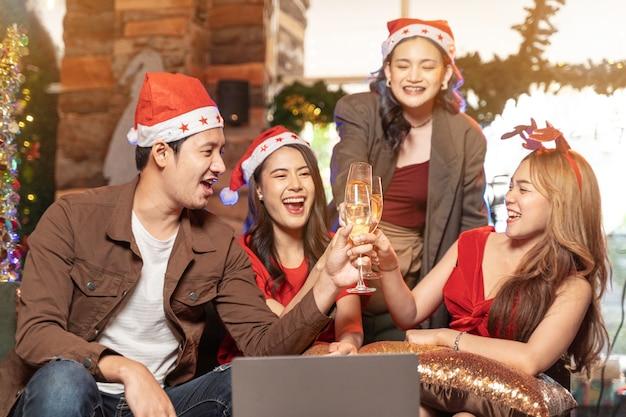 シャンパンのチャリンという音のクローズアップアジアの友人の女性と男性のパーティーを祝う