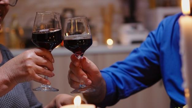 낭만적인 저녁 식사를 하는 동안 부딪히는 레드 와인 잔을 닫습니다. 행복한 노인 부부는 아늑한 주방에서 함께 식사를 하고 기념일을 축하하며 식사를 즐기고 있습니다.