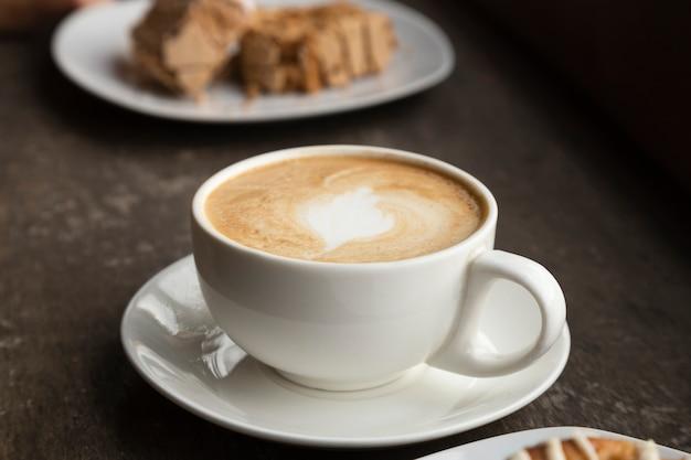 Крупный план кофейной чашки и сладостей