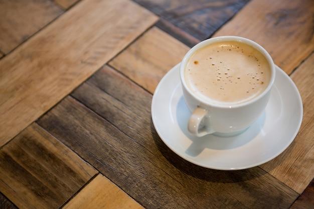 食堂の木製テーブルの上のコーヒーカップのクローズアップ