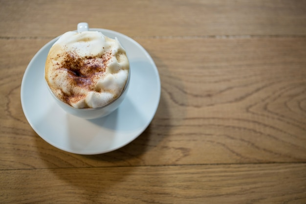 食堂のテーブルの上のクリーミーな泡とコーヒーカップのクローズアップ