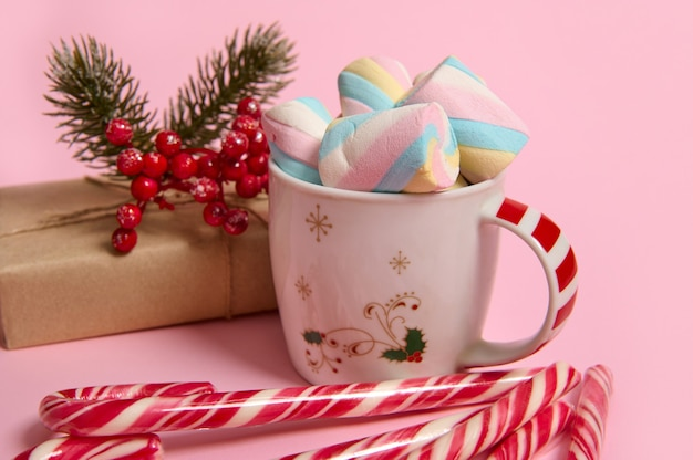 カラフルなマシュマロ、クラフト包装紙のクリスマスプレゼント、ピンクのパステルカラーの背景にヒイラギと縞模様のキャンディケインとコーヒーマグのクローズアップ。広告用のコピースペースとクリスマス、新年のコンセプト