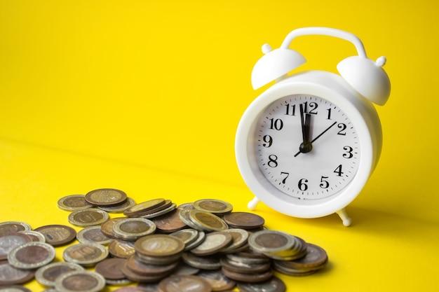 노란색 배경에 알람 시계에 의해 동전의 근접. 투자 개념입니다. 동전에 성장