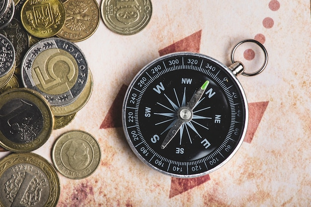 Крупным планом монет рядом с компасом