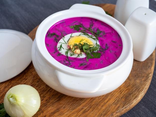Крупный план холодного супа хлодника на деревянной доске. суп польско-белорусской и русской кухни из свеклы и кефира, украшенный половинкой яйца. здоровая пища