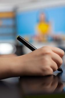 2つのディスプレイを備えたコンピューターを使用して顧客の写真を編集するグラフィックタブレット上を移動するスタイラス鉛筆を保持しているカラー女性レタッチャーのクローズアップ