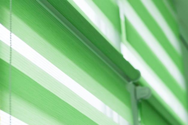 Крупным планом рулонные шторы из цветной ткани на окне. рулонные шторы.
