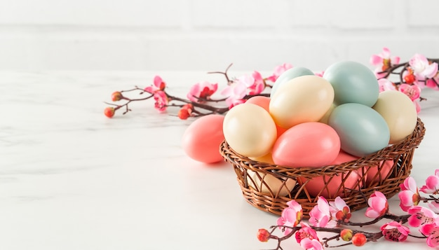 밝은 흰색 나무 테이블 배경에 분홍색 매 화 꽃 바구니에 다채로운 부활절 달걀 닫습니다.