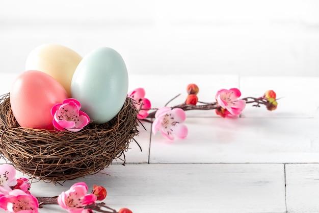 밝은 흰색 나무 테이블 배경에 분홍색 매 화 꽃과 둥지에 다채로운 부활절 달걀 닫습니다.