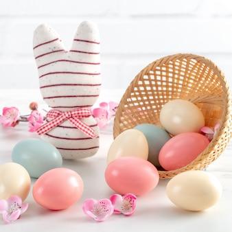밝은 흰색 나무 테이블에 분홍색 매 화 꽃과 둥지에서 다채로운 부활절 달걀 닫습니다.